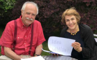 Michael Sells and Simone Fattal contributor photo, sitting at a metal table outside reading from a printer paper packet in front of hedge
