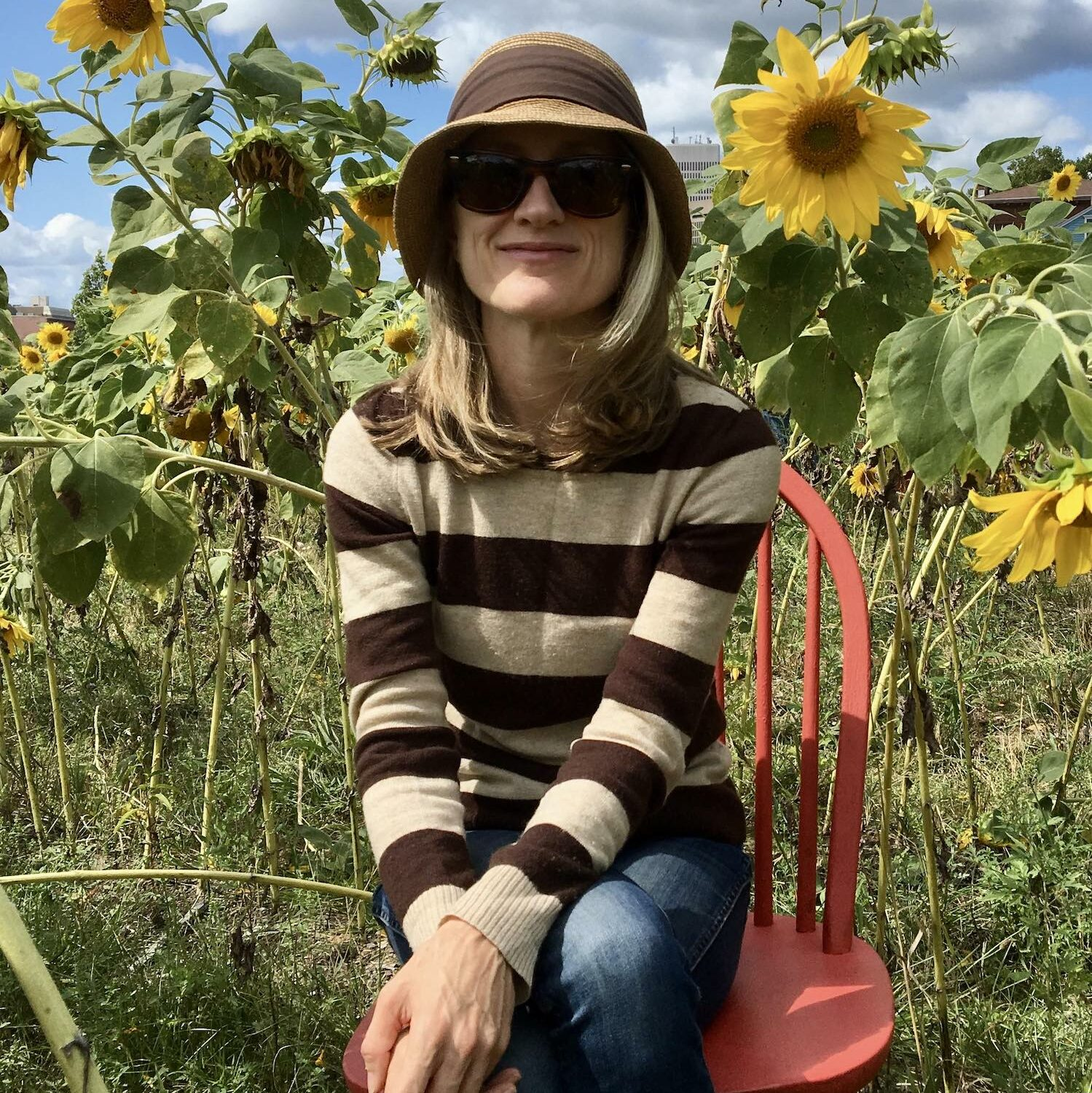 Kate Colby author photo in field of sunflowers