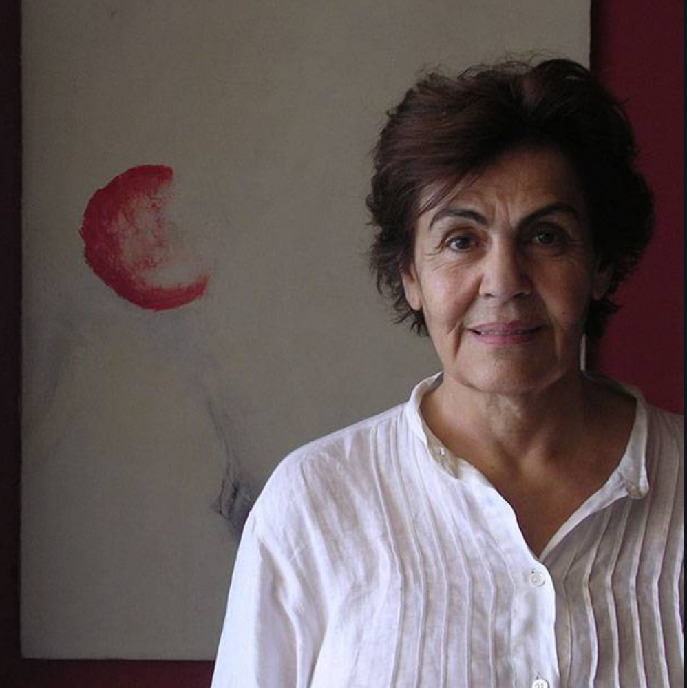 Simone Fattal contributor photo, indoors in front of painting with a red half-circle