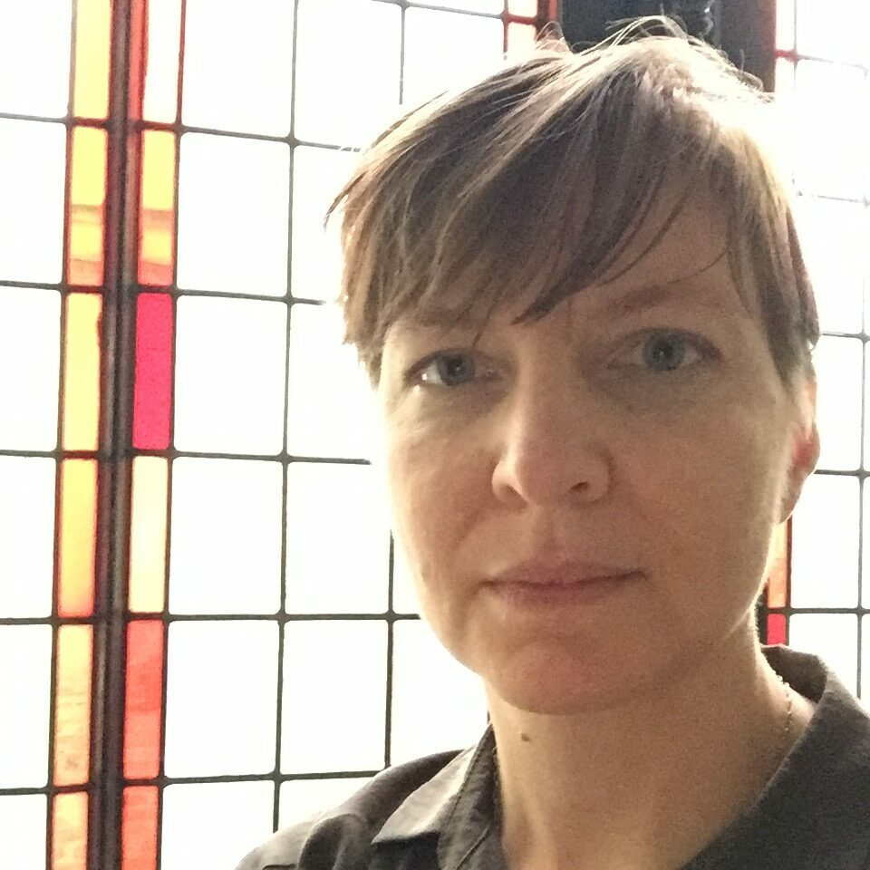 Tracy Grinnell author photo, indoors in front of stained glass window