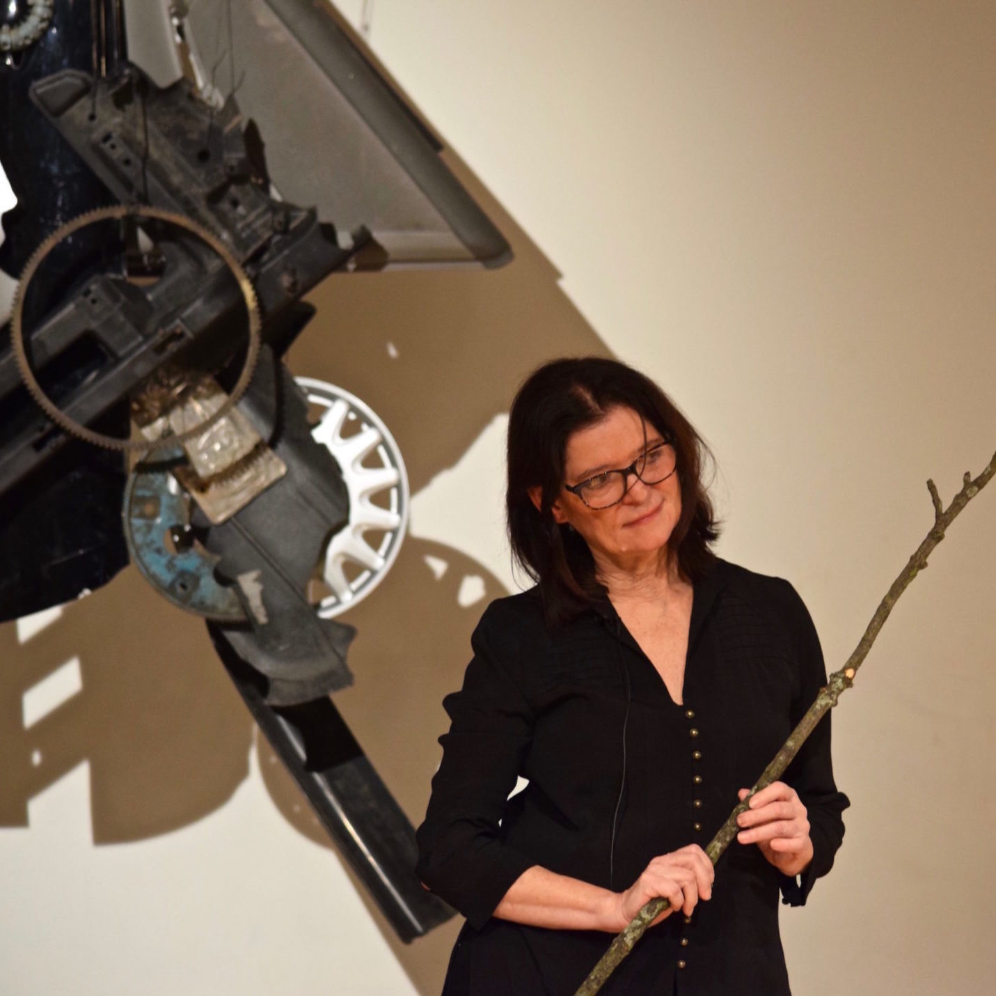 Carla Harryman author photo, indoors, holding a long stick, in front of a large metal machine