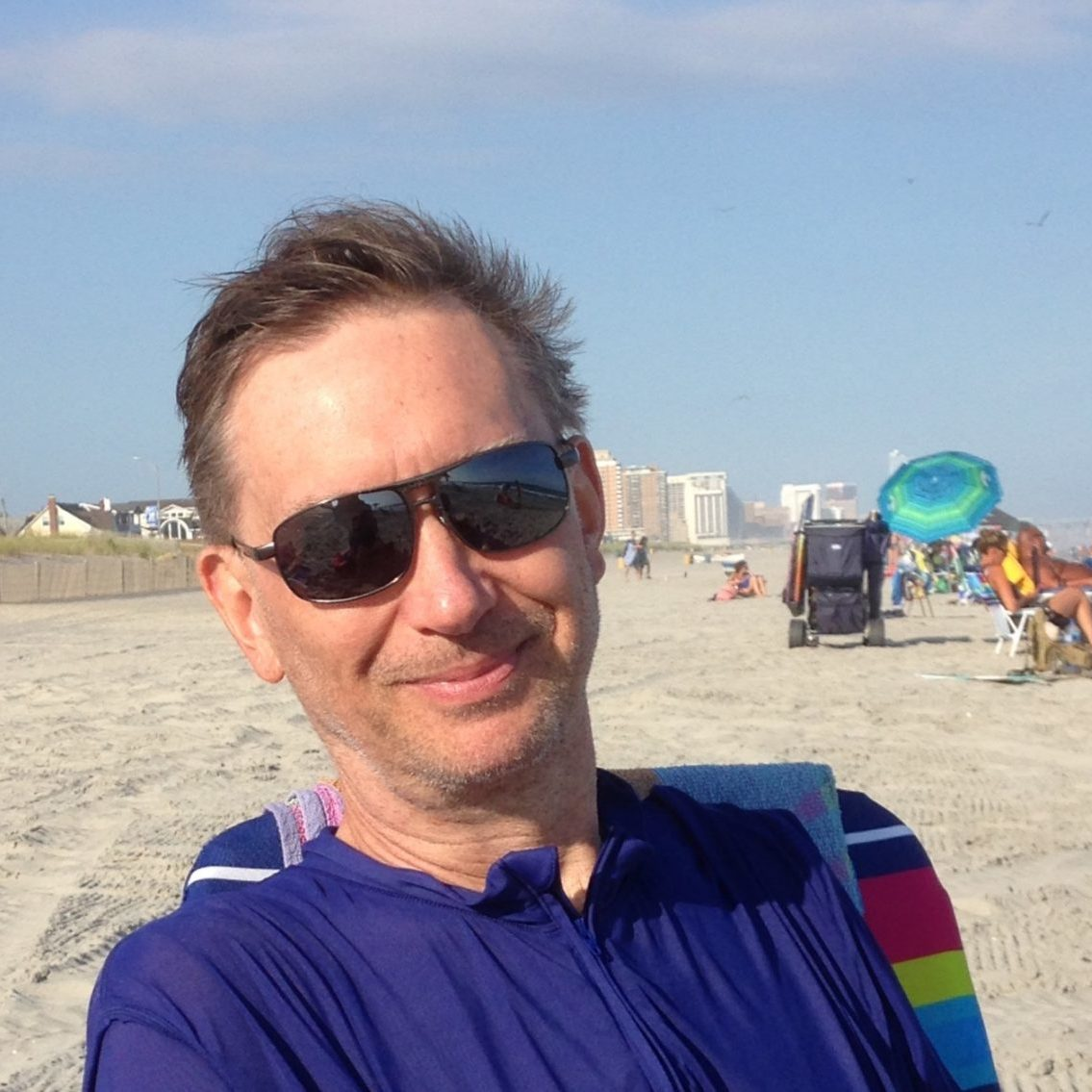 Andrew Levy author photo, at a beach, sitting in a beach chair, wearing sunglasses