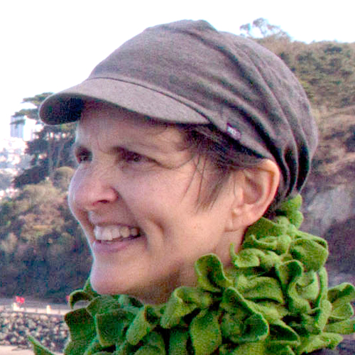 Mary Burger author headshot in green scarf with brown hat outdoors