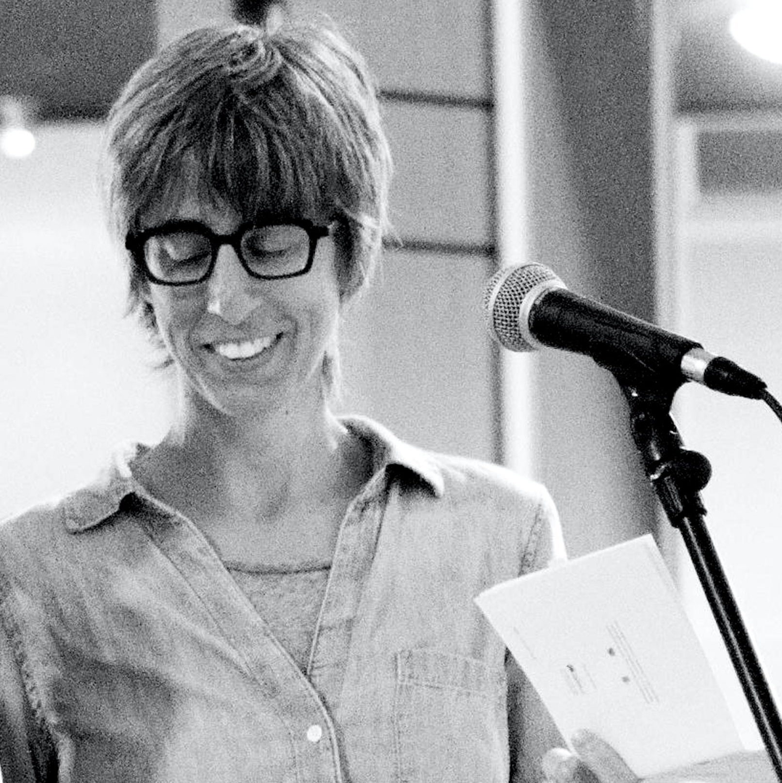 Nathanaël speaking into mic, black and white photo