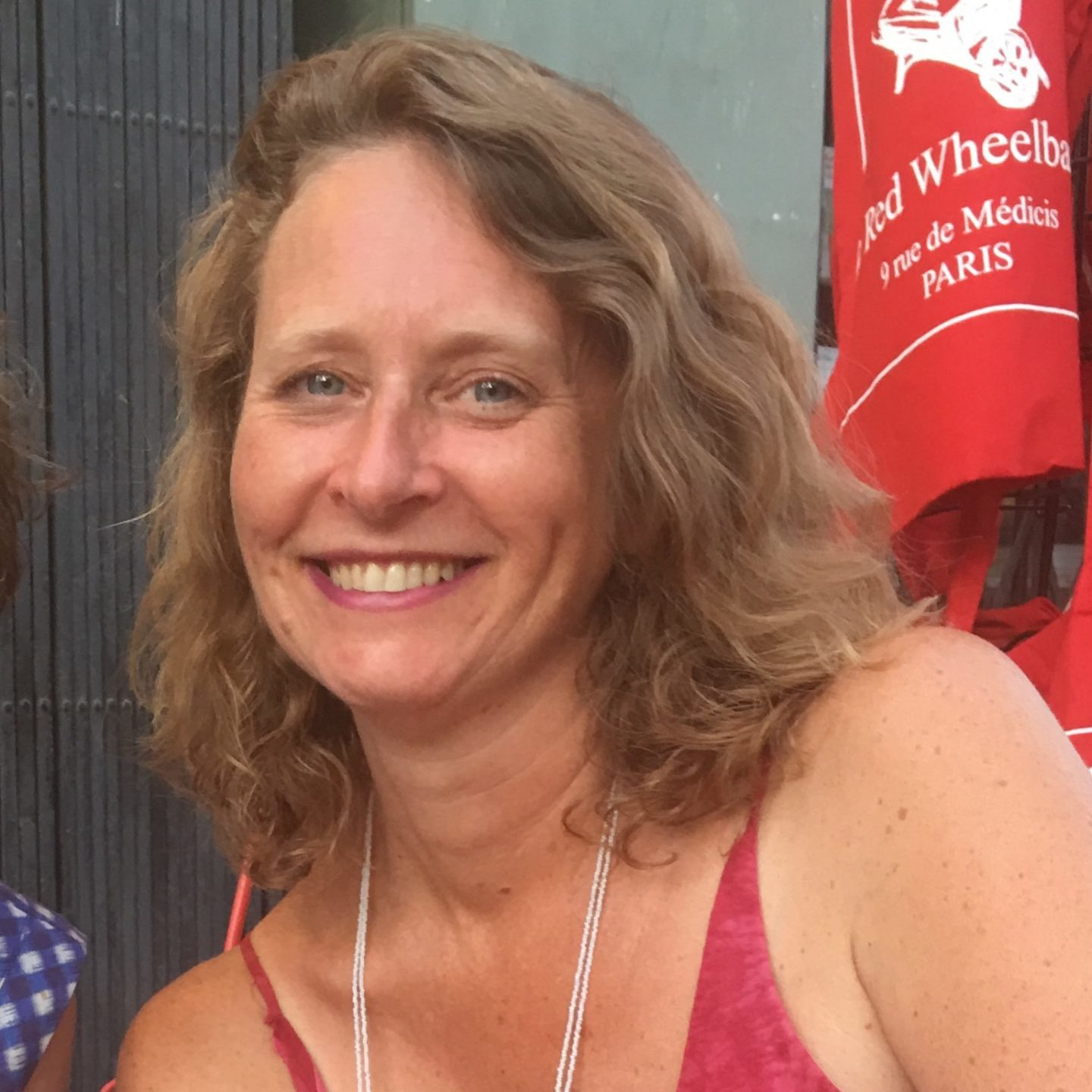 Sarah Riggs author photo, smiling in front of a red tote bag and a green wall