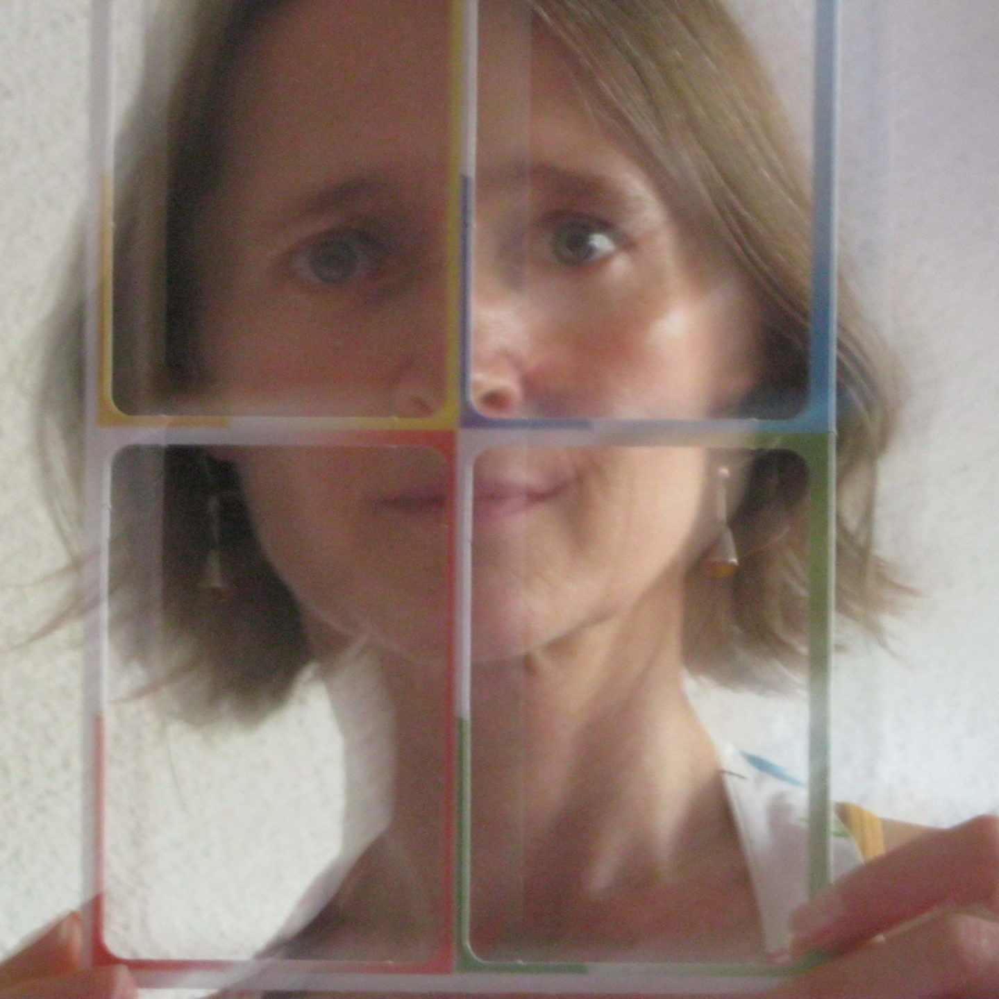 Lisa Samuels author photo, holding a colorful cardboard cut out of four rectangle outlines in front of her face