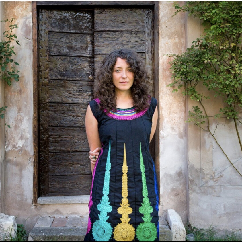 Jennifer Scappettone contributor photo, outdoors, arms behind her back, in front of stone building with large wooden doors