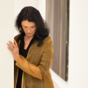 Anne Waldman author photo, indoors, looking down, her hand on the corner of a white wall