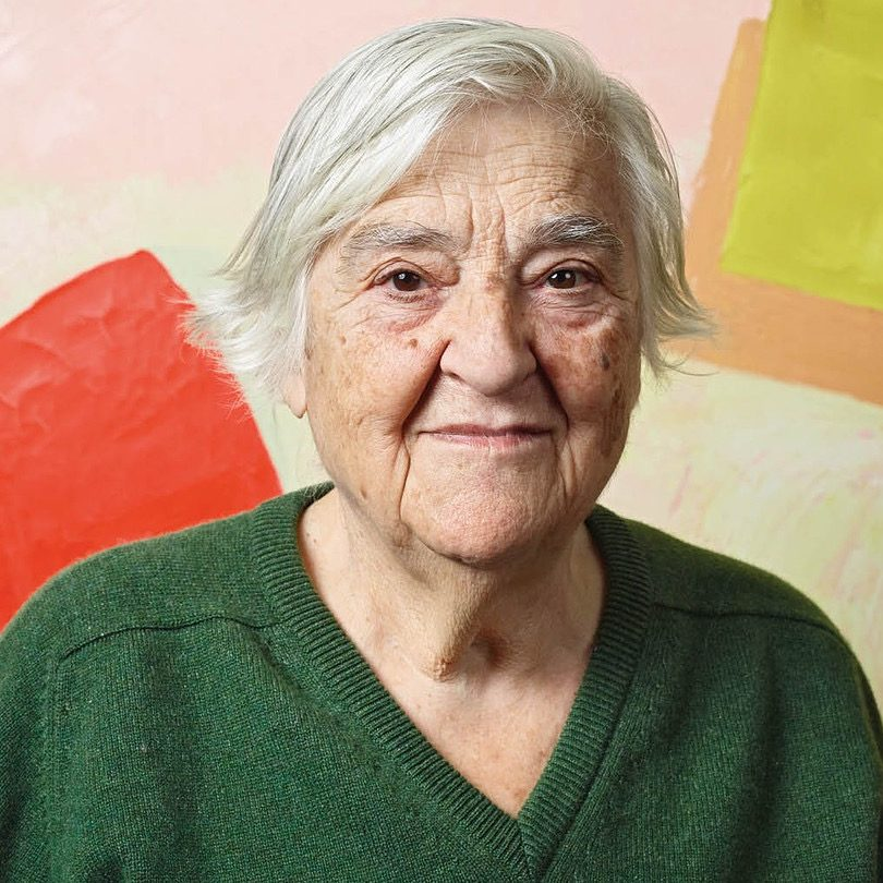 Etel Adnan contributor photo, in front of painting with colorful squares