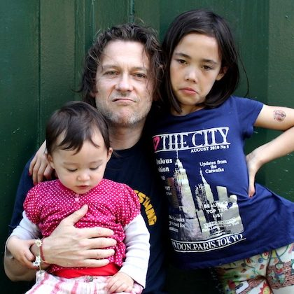 Tim Atkins contributor photo with his two children, outdoors in front of wooden green wall