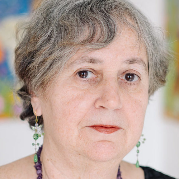 Susan Bee contributor photo, close-up of face in front of blurred white wall with colorful art