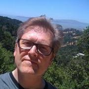 steve dickison contributor photo, outdoors in front of tree-filled valley and blue skyline