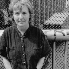 Fanny Howe author photo, b&w in front of chain link fence