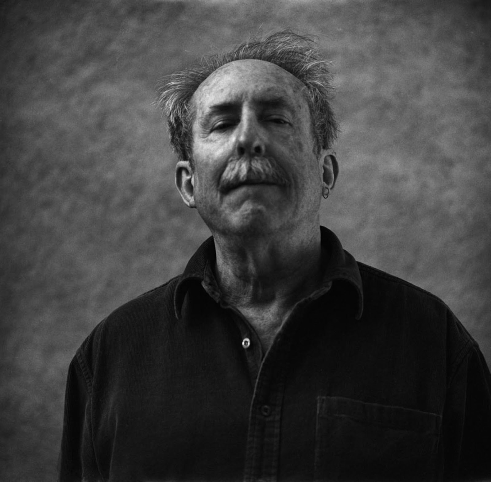 Tom Raworth contributor photo, b&w in front of textured wall