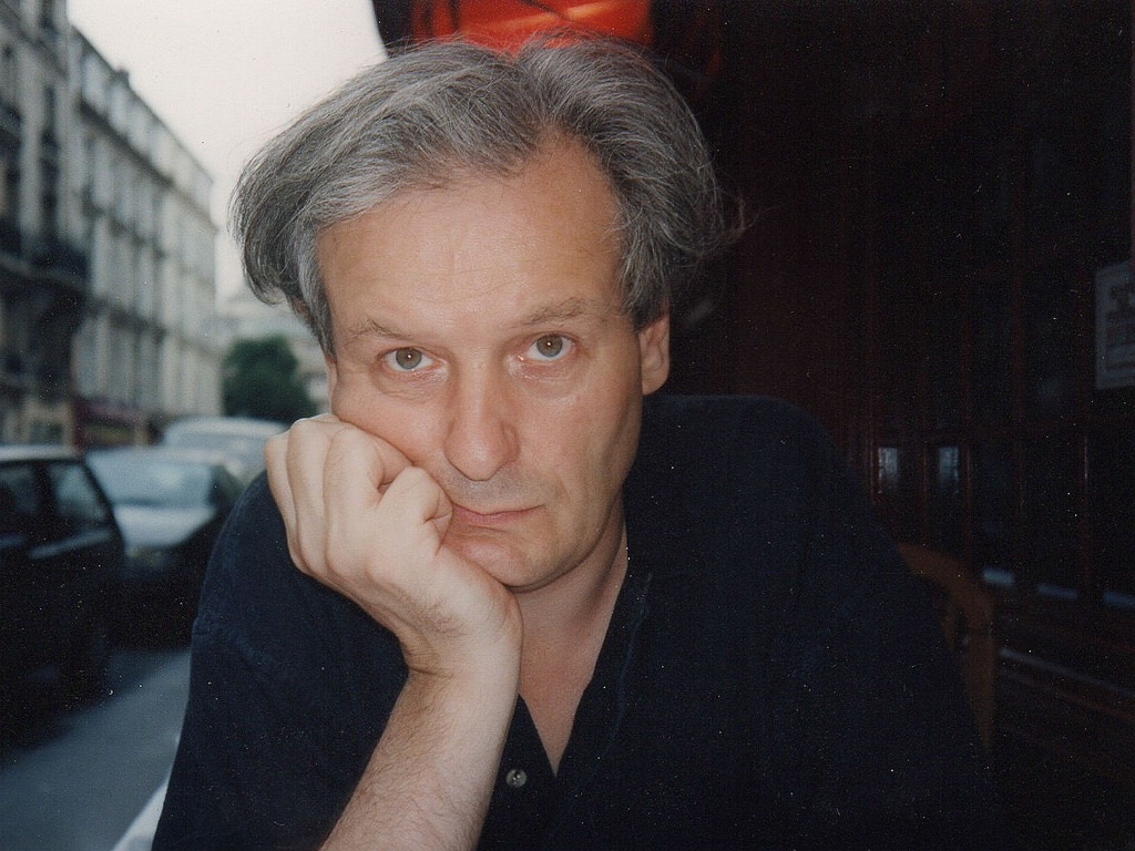 Claude Royet-Journoud contributor photo, sitting beside a wooden building and a city street