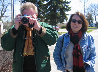 Juliette Valéry contributor photo; outdoors on city street beside a man looking into the camera through a film camera