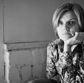 Magdalena Zurawski contributor photo; b&w in front of a brick and wood wall