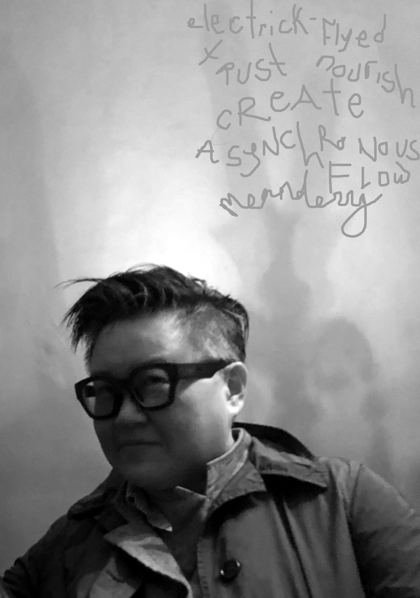 Kyoo Lee contributor photo, black and white photo, plain background with handwritting on the wall that says, electrick-flyed trust nourish create asynchronous flow meanderry