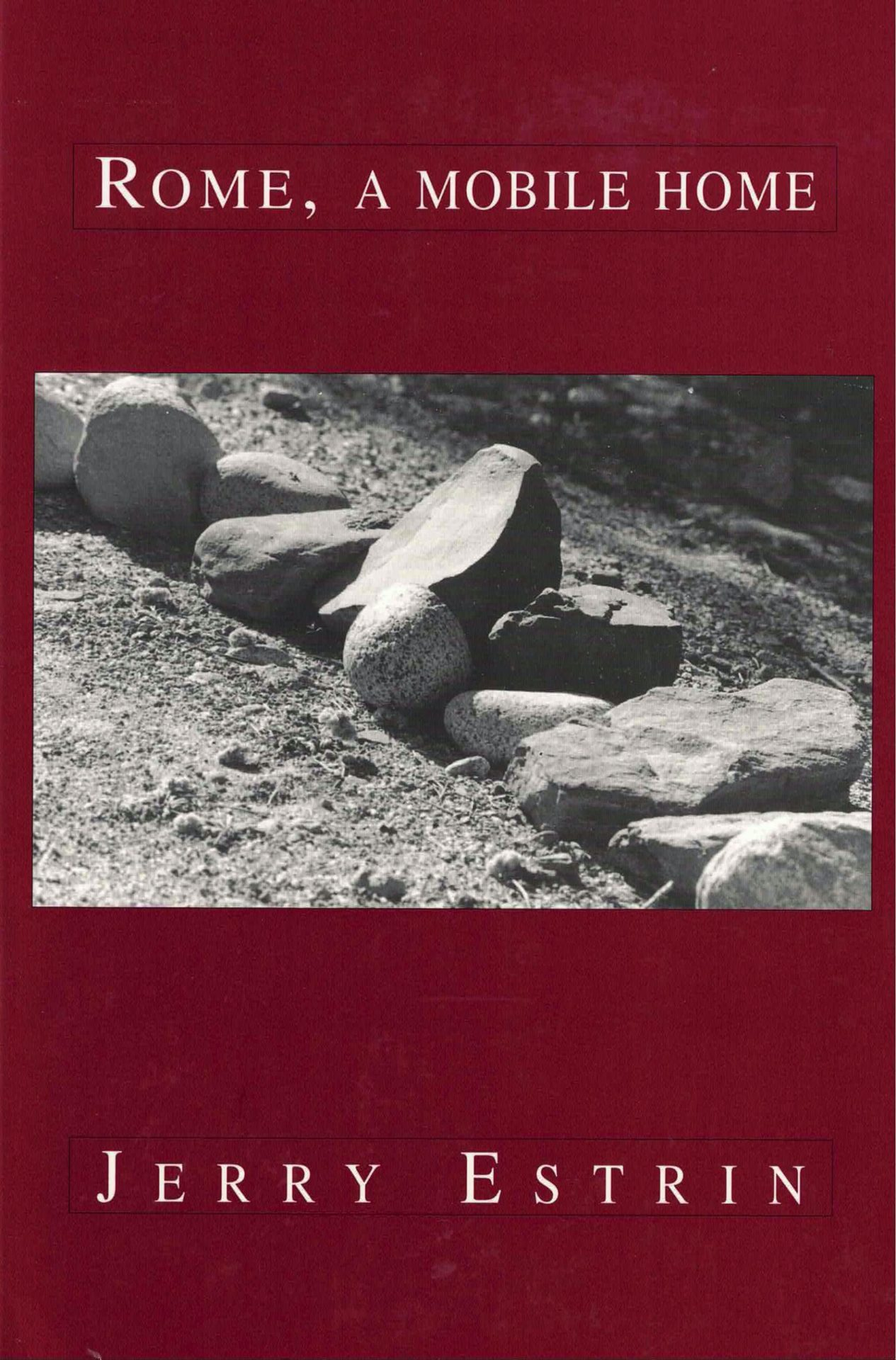 cover of Rome, A Mobile Home by Jerry Estrin, dark red background with horizontal b&w close-up photo of a line of stones in sand