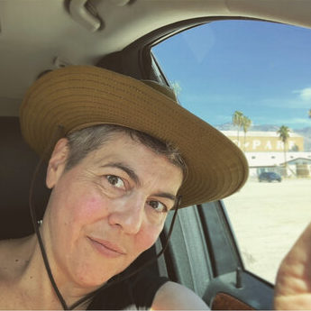 Stacy Szymaszek controbutor photo, wearing a sun hat and sitting in a car