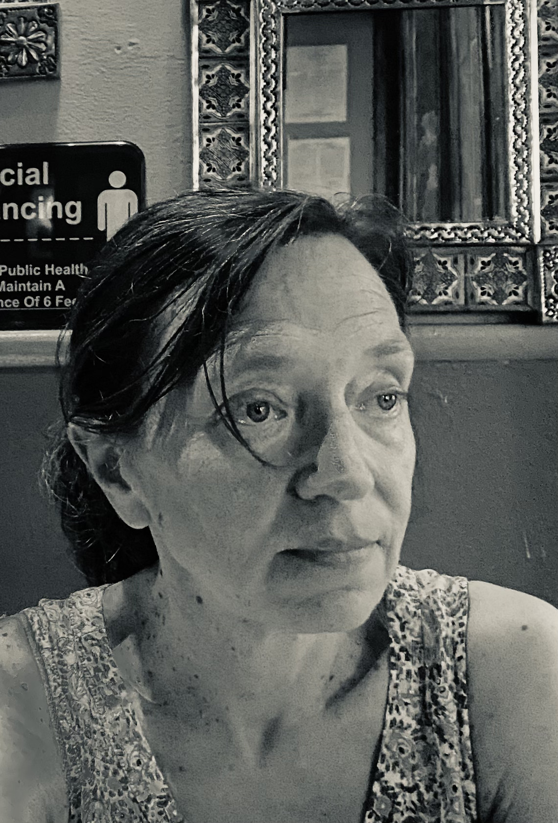 Headshot of Eléna Rivera seated in a restaurant booth in black and white